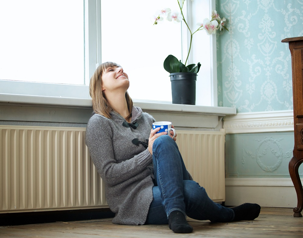 woman resting on heater with mug